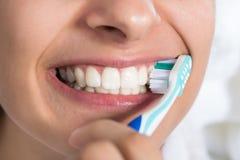Denti di spazzolatura della donna a casa immagine stock