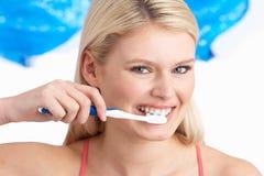 Denti di spazzolatura della giovane donna in studio fotografia stock