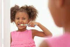 Denti di spazzolatura della ragazza afroamericana sveglia e guardare in specchio in bagno immagine stock libera da diritti