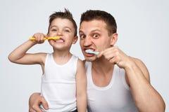 Denti di spazzolatura divertenti del figlio e del padre immagine stock
