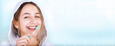 Denti di spazzolatura felici della giovane donna immagini stock