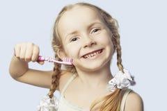 Denti di spazzolatura sorridenti della bambina fotografia stock libera da diritti