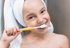 Denti di spazzolatura sorridenti della bambina immagini stock