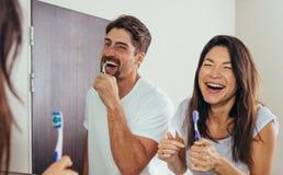 Denti di spazzolatura sorridenti delle coppie in bagno fotografie stock