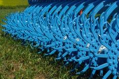 Denti e nodi di un erpice rotatorio che sta sull'erba immagini stock libere da diritti