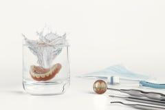 Denti sullo specchio accanto alle protesi dentarie in acqua Fotografie Stock