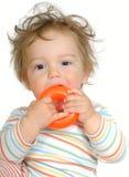 Dentición del bebé en el anillo plástico anaranjado Foto de archivo libre de regalías