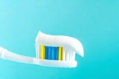 Dentifricio in pasta su un primo piano dello spazzolino da denti su un fondo blu Fotografia Stock