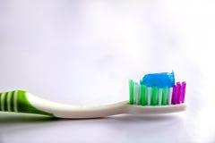 Dentifricio in pasta su un primo piano dello spazzolino da denti su un fondo della luce bianca Immagini Stock
