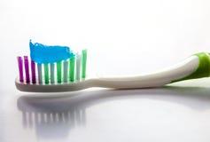 Dentifricio in pasta su un primo piano dello spazzolino da denti su un fondo della luce bianca fotografie stock