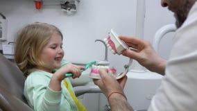 Dentis enseña a una muchacha a cepillar sus dientes correctamente almacen de metraje de vídeo