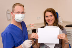 Dentist. A happy woman shows a card Stock Image