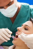At the Dentist. Young woman receiving dental care Royalty Free Stock Photos