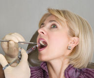 At the dentist. The dentist does an injection to the young woman Royalty Free Stock Image