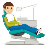 At the Dentist. Young man sitting on the dentist chair waiting the doctor Stock Image
