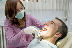 Dentist. Young female dentist examining patient