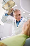Dentist adjust searchlight to illumine patient's mouth Royalty Free Stock Photo