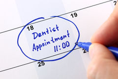Dentist appointment. Human hand writes reminder Dentist appointment 11-00 in calendar royalty free stock images