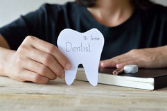 Dentist appointment in paper cuts tooth shape in woman hand Royalty Free Stock Photography