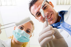 Dentist and assistant. Male dentist and assistant looking down at patient royalty free stock photography