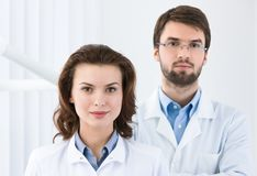Dentist and the assistant. Dentist and his assistant is waiting for the patient, white background Stock Photo