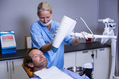Dentist assistant adjusting light over patients mouth Stock Image