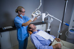 Dentist assistant adjusting light over patients mouth Stock Photos