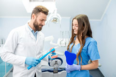 Dentist with assistant at the dental office. Handsome dentist showing how to brush teeth on artificial jaw to the young female student at the dental office Stock Photos