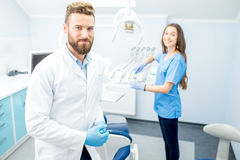 Dentist with assistant at the dental office. Handsome dentist with young female assistant in uniform prepairing for the job at the dental office Royalty Free Stock Photo