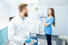 Dentist with assistant at the dental office. Handsome dentist with young female assistant in uniform prepairing for the job at the dental office Royalty Free Stock Image