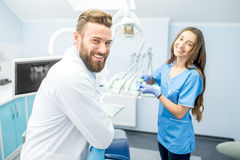 Dentist with assistant at the dental office. Handsome dentist with young female assistant in uniform prepairing for the job at the dental office Stock Photo