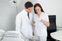 Dentist And Assistant With Dental Report Royalty Free Stock Images