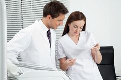 Dentist And Assistant With Dental Report. Male dentist with assistant discussing report in clinic Stock Images