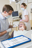 Dentist and assistant in exam room with woman Royalty Free Stock Image