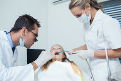 Dentist  with assistant examining girls teeth Royalty Free Stock Photo