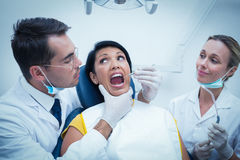 Dentist with assistant examining womans teeth Stock Image