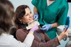 Dentist with assistant and female patient checking and selecting colour of the teeth in dental clinic office. Doctor is making the process of treatment Stock Photography