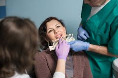 Dentist with assistant and female patient checking and selecting colour of the teeth in dental clinic office. Doctor is making the process of treatment Royalty Free Stock Photos