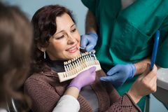 Dentist with assistant and female patient checking and selecting colour of the teeth in dental clinic office. Doctor is making the process of treatment Stock Images