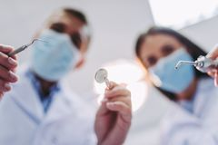 Dentist and assistant holding dental tools stock photos