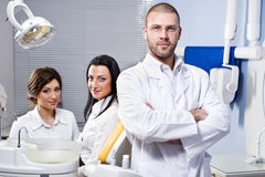 Dentist, assistant and patient. Friendly male dentist, assistant and smiling patient at dental clinic Royalty Free Stock Image