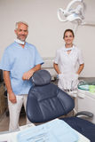 Dentist and assistant smiling at camera inviting you to the chair Stock Images