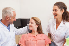 Dentist and assistant smiling with patient in chair Royalty Free Stock Images