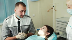 Dentist and assistant speaking with client before treating. stock video