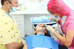 Dentist and assistant treated teeth to girl Royalty Free Stock Photography