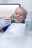 Dentist assisting young patient while brush teeth Stock Image