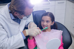 Dentist assisting young patient while brush teeth Stock Images