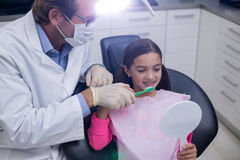 Dentist assisting young patient while brush teeth Royalty Free Stock Images