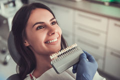 At the dentist. Beautiful young woman is sitting in dentist`s chair while doctor is examining her teeth royalty free stock images
