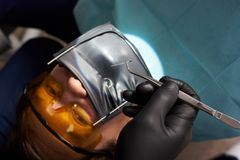 Dentist in black gloves holds tweezers over patient using cofferdam. Dentist in black gloves holds tweezers over a patient using a cofferdam. Close-up. Treatment Stock Images